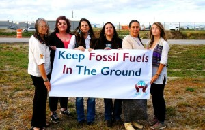 Members of the Women's Earth and Climate Action Network and Movement Rights stand with Kandi Mossett (center) outside of a 'man-camp' in Williston, ND. Photo credit: Emily Arasim Members of the Women's Earth and Climate Action Network and Movement Rights stand with Kandi Mossett (third from right) outside of a 'man-camp' in Williston, North Dakota. Photo credit: Emily Arasim